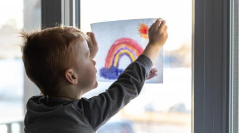 Child hanging painting on a window