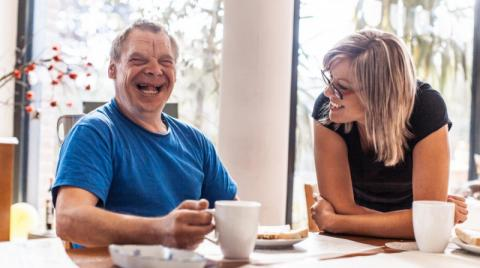 Person with a disability sitting with his caregiver