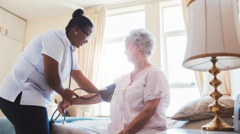 Elderly person having blood pressure checked by in home nurse