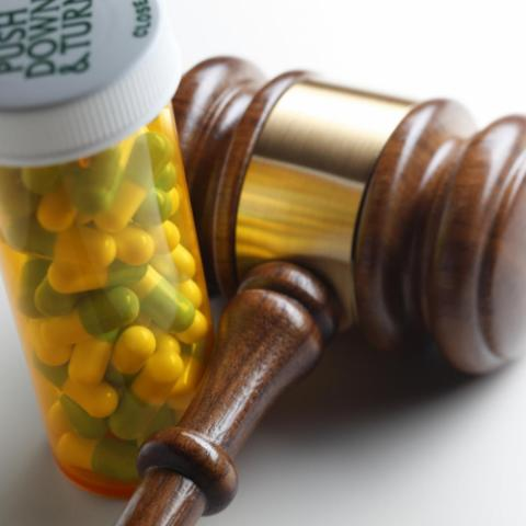 Gavel next to a bottle of pills