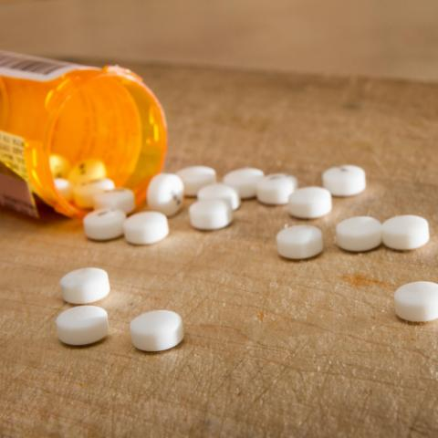 Pill bottle and pills on wooden table
