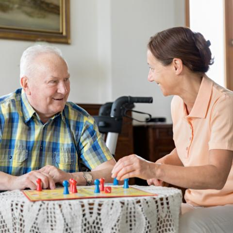 Senior man and home caregiver playing board game