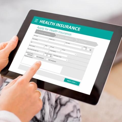 Person applying for health insurance on a tablet.