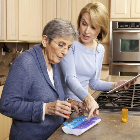 Community health worker helping woman with medications