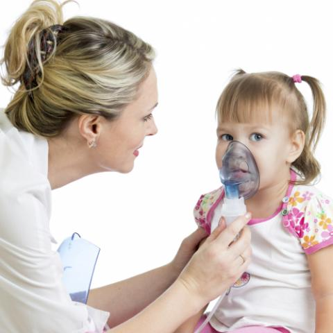 Doctor helping child with asthma