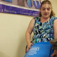 Woman with disabilities shows blue wrap bag she made