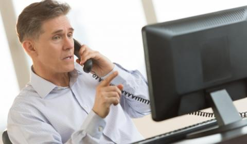 Man using landline and working on computer