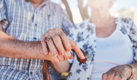 Two elderly people holding hands on a cane