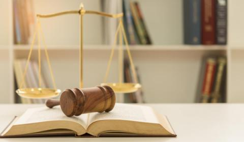 Gavel on a book with scales in the background