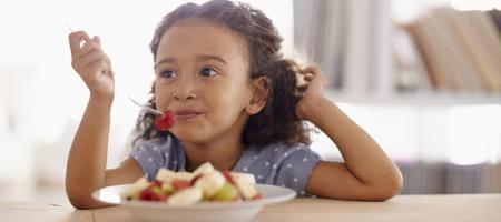 child eating a healthy snack of assorted fruits