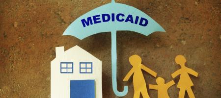 paper cut-out of family underneath small umbrella with medicaid written on it