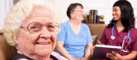 Elderly woman sits with in home caretakers