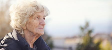 Nostalgic elderly woman gazes toward the sky