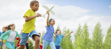 children running with a toy airplane