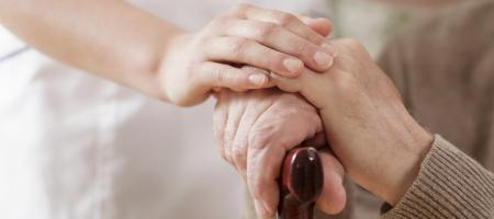 Nurse with hands on an elderly persons