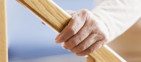 Elderly persons hand on a wooden rail