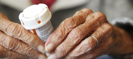 Elderly person holding a pill container