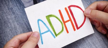boy holding note card that reads adhd