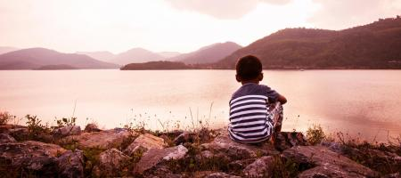 Boy sitting in front of dam overlooking a lake